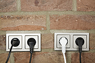 Plugs in wall socket, close-up - GWF00673