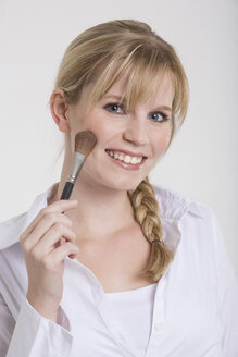 Young woman using a make-up brush - RDF00880