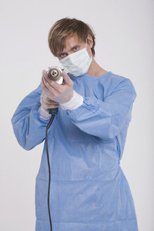 Young doctor holding a power drill - RDF00865