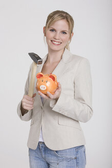Young woman holding a piggybank and a hammer - RDF00844
