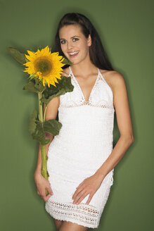 Young woman holding a sunflower, portrait - RDF00767