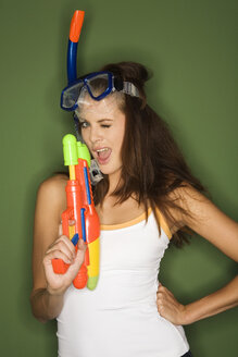 Young woman wearing diving goggles, holding a water pistol - RDF00761