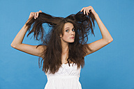 Young woman tearing her hair, portrait - RDF00752