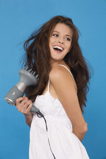 Young woman using hair blower, portrait - RDF00749