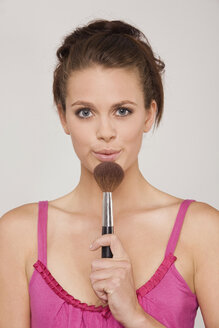 Young woman holding a makeup brush - RDF00728