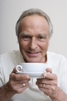 Senior man holding cup of coffee, portrait - WESTF08370