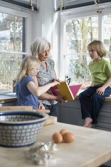 Grandmother and grandchildren (8-9) in the kitchen - WESTF08298