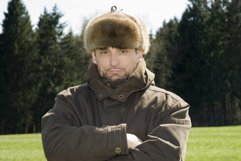 Germany, Bavaria, Man with fur cap, portrait - NHF00775