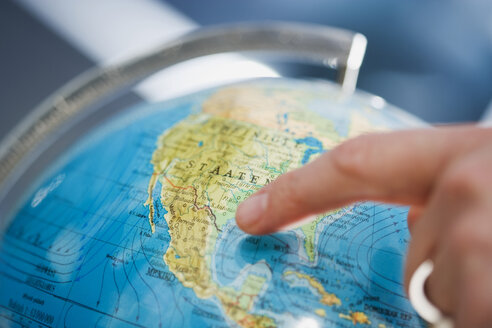 Person pointing at a globe - HKF00248