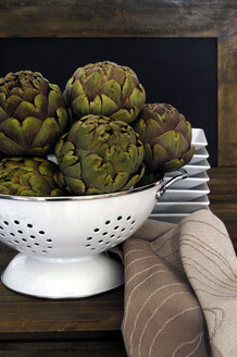 Artichokes in strainer on wooden table - 00446LR-U