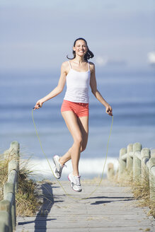 Young woman using skipping rope - ABF00321
