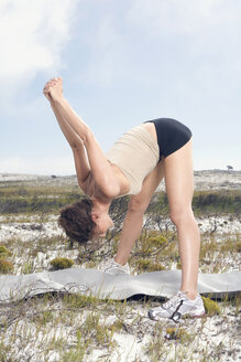 South Africa, Cape Town, Young woman exercising yoga - ABF00304