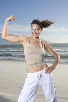 South Africa, Cape Town, Young woman flexing muscles, smiling, portrait - ABF00276