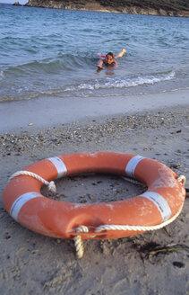 Italy, Sardinia, Tuaredda, Woman in sea waving for help - LFF00124
