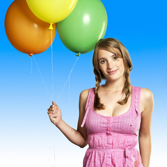 Teenage girl (16-17)  holding bunch of balloons, smiling, portrait - JLF00302