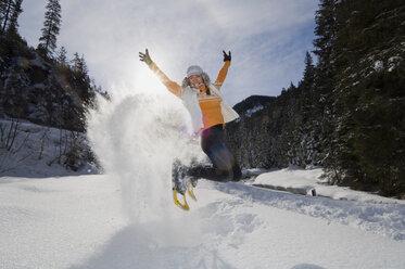 Austria, Salzburger Land, Altenmarkt-Zauchensee, Young woman jumping in snow - HH02526