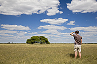 Africa, Botswana, Tourist looking at the landscape - FOF00721