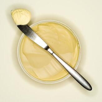 Margarine curl lying on back of a knife, elevated view - MUF00518