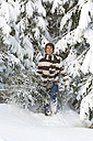 Austria, Salzburger Land, Altenmarkt, Young man carrying fir tree - HH02599