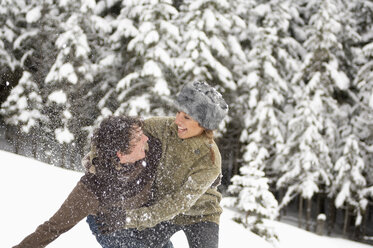 Austria, Salzburger Land, Young couple in snowscape, fooling around - HH02584