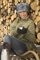 Austria, Salzburger Land, Altenmarkt, Young woman taking a break, holding cup - HH02572