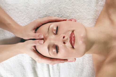 Young woman receiving facial massage, eyes closed, elevated view - RDF00916