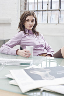 Young businesswoman sitting at desk, relaxing - BMF00377