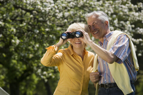 Germany, Baden Württemberg, Tübingen, Senior couple, senior woman looking through binoculars - WESTF08908