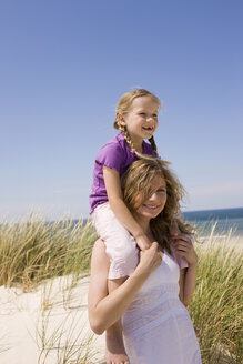 Germany, Baltic sea, Mother carrying daughter (6-7) on shoulders, portrait - WESTF09319