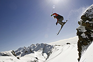Italy, Tyrol, Monte Rosa, Freeride, Man jumping on skis, low angle view - FFF00903