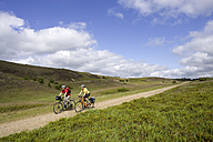 Denmark, Jutland, Couple mountain biking across farm track - DSF00180