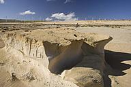 Spain, The Canary Islands, Man mountain biking across desert, wind park in background - DSF00174