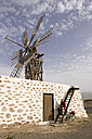 Spain, The Canary Islands, Man with mountain bike taking a break at windmill - DSF00168