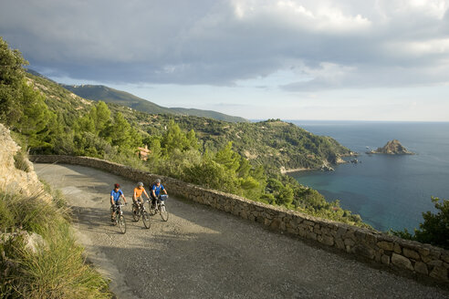 Italy, Tuscany, Monte Argentario, Three mountainbikers riding on coastal highway - DSF00147