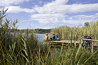 Italy, Tuscany, Lago dell'Accesa, Mountainbikers taking a break on the lakefront - DSF00144