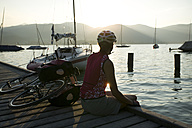 Germany, Bavaria, Tegernsee, Woman with mountainbike taking a break on landing stage - DSF00138