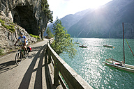 Austria, Tyrol, Achensee, Woman mountain biking lakeside - DSF00135