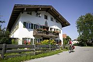 Germany, Bavaria, Lenggries, Woman mountain biking next  to residential house - DSF00132