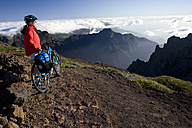 Spain, The Canary Islands, La Palma, Woman with mountain bike looking at mountain scenery - DSF00126