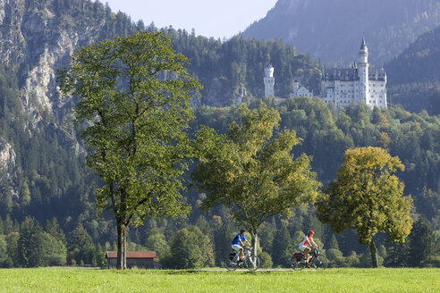 Germany, Bavaria, Neuschwanstein Castle, Couple mountain biking - DSF00117