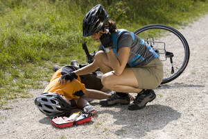 Germany, Bavaria, Oberland, Woman giving aid to fallen biker - DSF00108