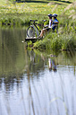 Germany, Bavaria, Couple with mountain bikes relaxing on lakeshore - DSF00105