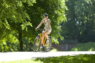 Germany, Bavaria, Munich, Woman mountain biking across park - DSF00099