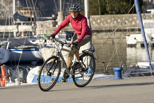 Italy, Trento, Riva del Garda, Female mountainbiker riding across pier - DSF00087