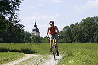 Germany, Bavaria, Oberland, Woman mountain biking, steeple in background - DSF00075