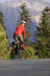 Austria, Tyrol, Ahornboden, Mountainbiker riding across highway - DSF00069