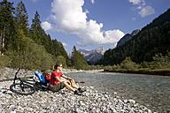 Austria, Tyrol, Ahornboden, Mountainbiker riding across highway - DSF00066