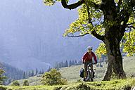 Austria, Tyrol, Ahornboden, Woman mountain biking - DSF00063