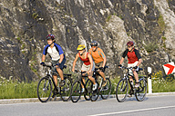 Germany, Bavaria, Sylvenstein, Four mountain bikers riding across highway - DSF00057