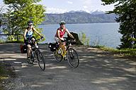 Germany, Bavaria, Walchensee, Two women mountain biking alongside lake - DSF00045